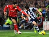 Steven Caulker of Cardiff City and Shane Long of West Bromwich Albion chase the ball during the Barclays Premier League match between Cardiff City and West Bromwich Albion at Cardiff City Stadium on December 14, 2013