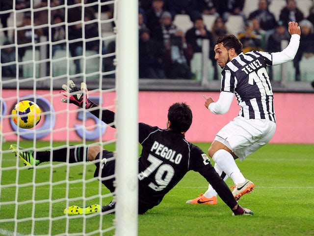 Carlos Tevez of Juventus scores the opening goal during the Serie A match between Juventus and US Sassuolo Calcio at Juventus Arena on December 15, 2013