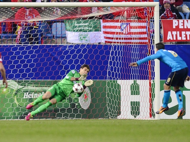 Atletico Madrid's goalkeeper Daniel Aranzubia stops a penalty by Porto's midfielder Josue Pesqueira during the UEFA Champions League Group G football match on December 11, 2013