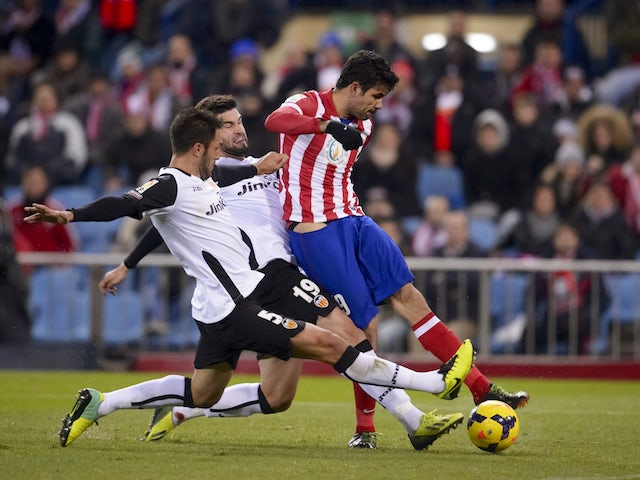 Atletico Madrid's Brazilian forward Diego da Silva Costa shoots to score during the Spanish league football match Club Atletico de Madrid vs Valencia CF at the Vicente Calderon stadium on December 15, 2013