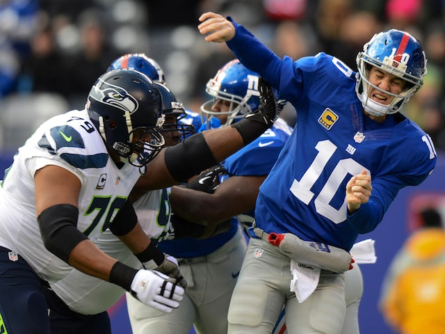 Quarterback Eli Manning of the New York Giants is hit as he throws a pass in the 1st half against the Seattle Seahawks at MetLife Stadium on December 15, 2013