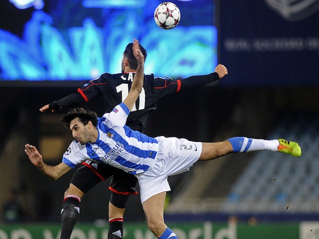 Leverkusen's midfielder Emre Can (L) vies with Real Sociedad's defender Carlos Martinez during the UEFA Champions League Group A football match Real Sociedad de Futbol vs Bayer 04 Leverkusen on December 10, 2013