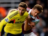 Fabio Borini of Sunderland is challenged by George McCartney of West Ham during the Barclays Premier League match between West Ham United and Sunderland at Boleyn Ground on December 14, 2013