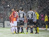 Galatasaray's and Juventus' players speak with referee Pedro Proenca after a heavy snow fall halted their UEFA Champions League group B football match at the TT Arena Stadium on December 10, 2013