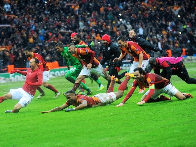 Galatasaray players slide at the Turk Telecom Arena to celebrate their victory over Juventus in the Champions League on December 11, 2013