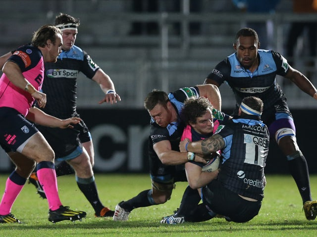 Rory Watts-Jones of Cardiff is tackled by Tyrone Holmes of Glasgow and Ryan Grant of Glasgow during the The Heineken Cup Pool 2 Match between Glasgow Warriors and Cardiff Blues at Scotstoun Stadium, on December 13, 2013