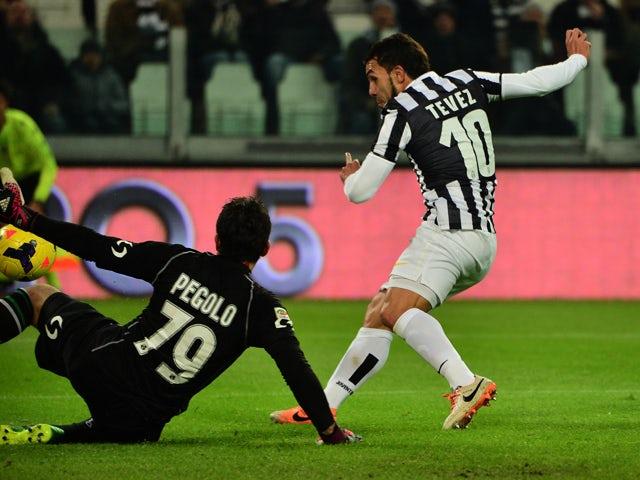 Juventus' Argentinian foward Carlos Alberto Tevez kicks and scores during their Serie A match Juventus vs Sassuolo at 'Juventus Stadium' in Turin on December 15, 2013