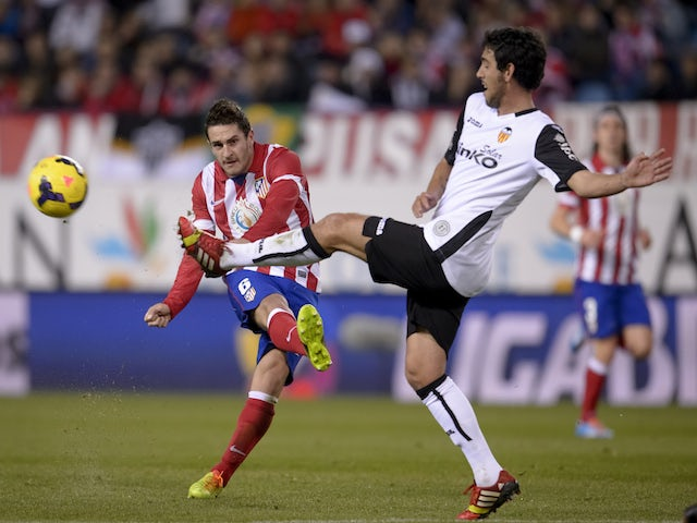Atletico Madrid's midfielder Koke vies with Valencia's midfielder Daniel Parejo during the Spanish league football match Club Atletico de Madrid vs Valencia CF at the Vicente Calderon on December 15, 2013