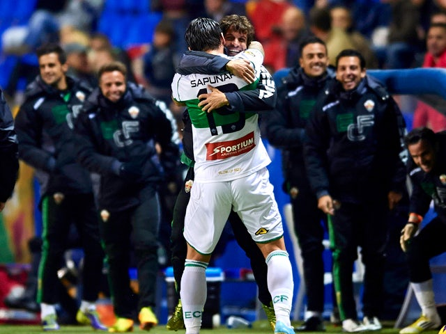 Sapunaru of Elche FC celebrates after scoring with his teammate Alberto Rivera during the La Liga match between Levante UD and Elche FC at Ciutat de Valencia on December 13, 2013