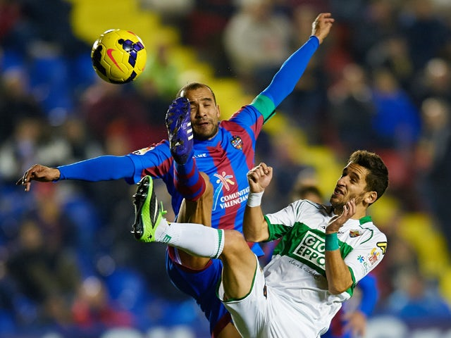 Juanfran Garcia of Levante UD competes for the ball with Ferran Corominas of Elche FC during the La Liga match between Levante UD and Elche FC at Ciutat de Valencia on December 13, 2013