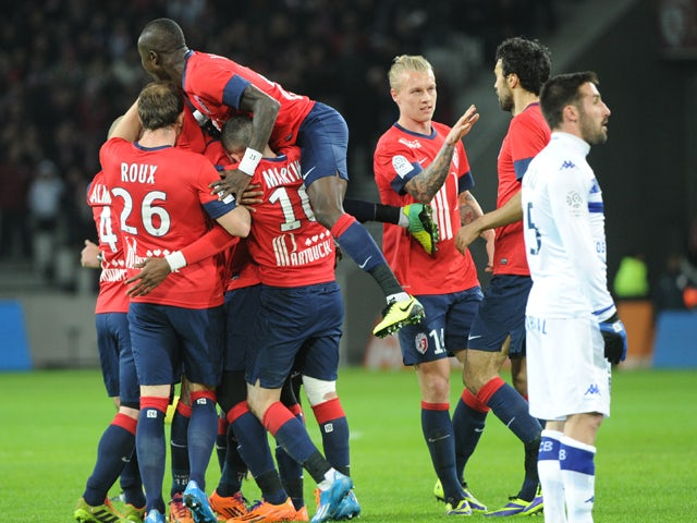 Lille's Ivorian forward Salomon Kalou is congratulated by teammates after scoring during the French L1 football match Lille vs Bastia on December 15, 2013