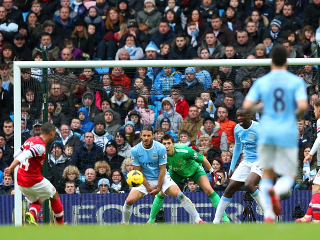 Theo Walcott of Arsenal scores their first goal past Costel Pantilimon of Manchester City during the Barclays Premier League match between Manchester City and Arsenal at Etihad Stadium on December 14, 2013