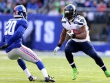 Marshawn Lynch of the Seattle Seahawks carries the ball as Prince Amukamara of the New York Giants defends at MetLife Stadium on December 15, 2013