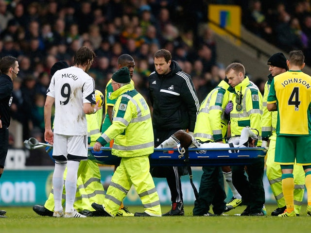 Nathan Dyer of Swansea City is carried off the pitch on a stretcher after being injured during the Premier League match between Norwich City and Swansea City at Carrow Road on December 15, 2013