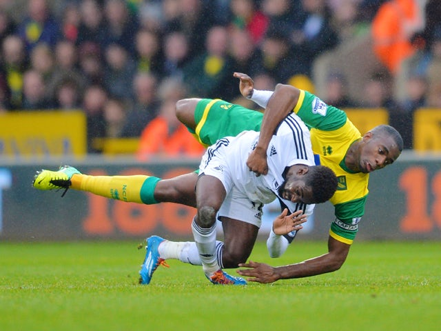 Nathan Dyer of Swansea looks in pain as he lands on his ankle and later leaves the field on a stretcher after Seb Bassong of Norwich lands on top of him after they both go for the header during the Barclays Premier League match between Norwich City and Sw