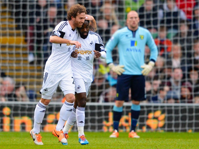 Nathan Dyer of Swansea is congratulated by his team mate Jose Canas after he scores their first goal during the Barclays Premier League match between Norwich City and Swansea City at Carrow Road on December 15, 2013