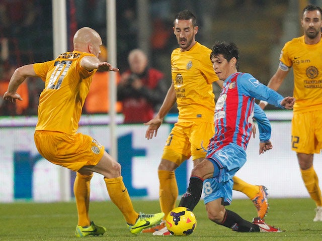Pablo Barrientos (R) of Catania competes for the ball with Emil Halfredsson of Hellas Verona during the Serie A match on December 14, 2013