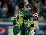 Umar Akmal congratulate Sharjeel Khan during the second Twenty20 International match between Pakistan and Sri Lanka at Dubai Sports City Cricket Stadium on December 13, 2013