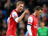 Per Mertesacker of Arsenal has words with Mesut Ozil of Arsenal during the Barclays Premier League match between Manchester City and Arsenal at Etihad Stadium on December 14, 2013
