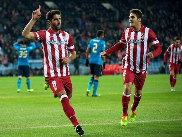 Raul Garcia celebrates scoring their opening goal with teammate Koke during the UEFA Champions League Group G match at Vicente Calderon Stadium on December 11, 2013