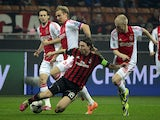 AC Milan's midfielder Riccardo Montolivo fights for the ball with Ajax's midfielder Davy Klaassen during the group H Champions League football match AC Milan vs Ajax, on December 11, 2013