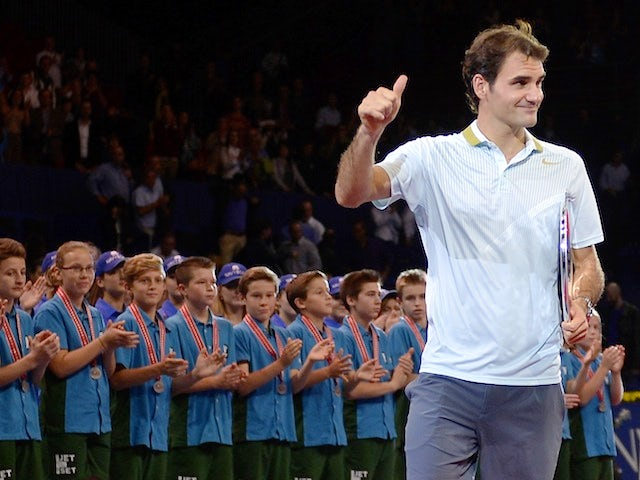 Roger Federer gives a thumbs-up after collecting the runner-up trophy at the Swiss Indoors ATP tennis tournament in Basel on October 27, 2013