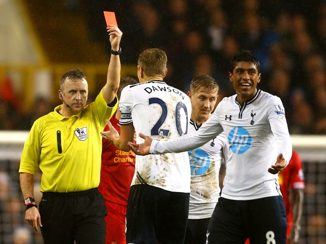 Referee Jonathan Moss shows Paulinho of Tottenham Hotspur a red card for a foul on Luis Suarez of Liverpool during the Barclays Premier League match between Tottenham Hotspur and Liverpool at White Hart Lane on December 15, 2013