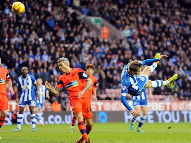 Nick Powell of Wigan Athletic scores the second goal of the game for his side during the Sky Bet Championship match between Wigan Athletic and Bolton Wanderers at the DW Stadium on December 15, 2013