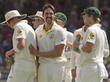 Australian bowler Mitchell Johnson celebrates with teammates after dismissing England batsman Joe Root on the fourth day of the third Ashes cricket Test match in Perth on December 16, 2013