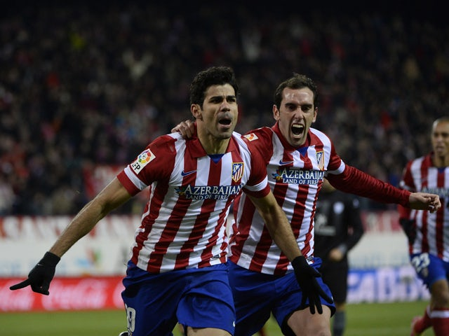 Atletico Madrid's Brazilian forward Diego da Silva Costa celebrates after scoring with Atletico Madrid's Uruguayan defender Diego Godin during the Spanish league football match Club Atletico de Madrid vs Levante UD at the Vicente Calderon stadium in Madri