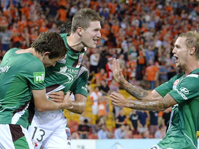 Joseph Gibbs of the Jets celebrates with team mates after scoring a goal to seal the victory during the round 11 A-League match between Brisbane Roar and the Newcastle Jets at Suncorp Stadium on December 20, 2013