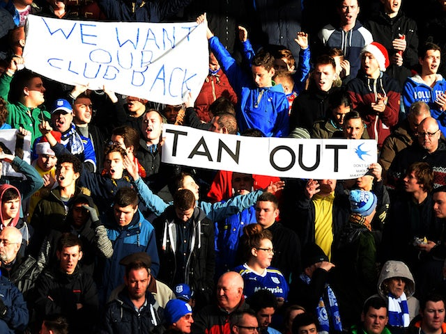 Cardiff City supporters hold banners opposing their club's Malaysian owner Vincent Tan during the English Premier League football match against Liverpool on December 21, 2013