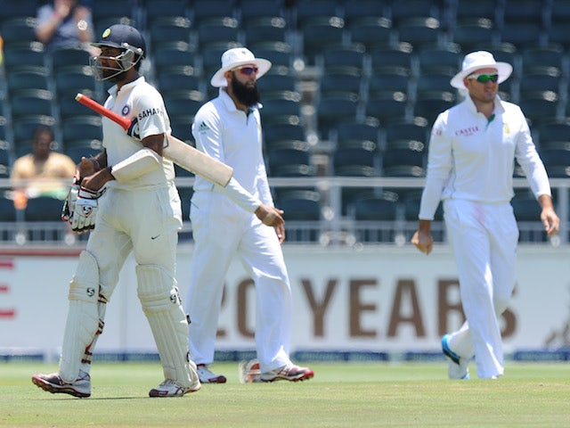 Indian batsman Cheteshwar Pujara walks off the field after being bolwed by South African bowler Jacques Kallis on the fourth day of a cricket Test match on December 21, 2013