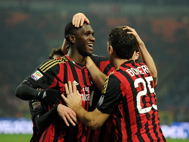 Milan's Cristian Zapata is congratulated by teammates after scoring his team's opening goal against Roma during their Serie A match on December 16, 2013
