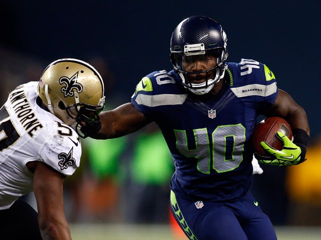 Fullback Derrick Coleman #40 of the Seattle Seahawks carries the ball as outside linebacker David Hawthorne #57 of the New Orleans Saints defends during a game at CenturyLink Field on December 2, 2013