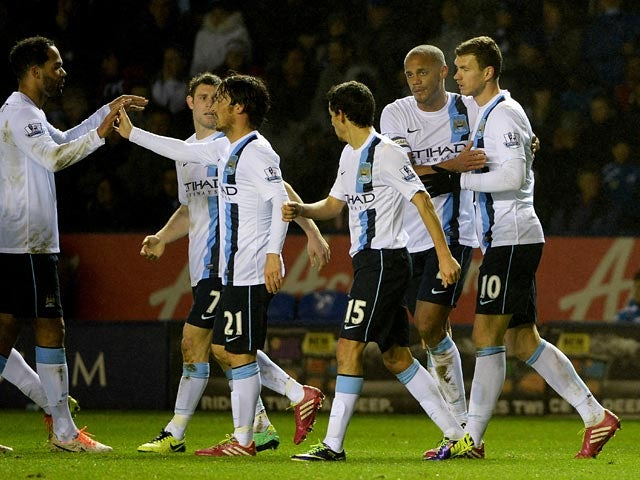 Man City's Edin Dzeko is congratulated by teammates after scoring his team's second goal against Leicester during their Capital One Cup quarter-final match on December 17, 2013