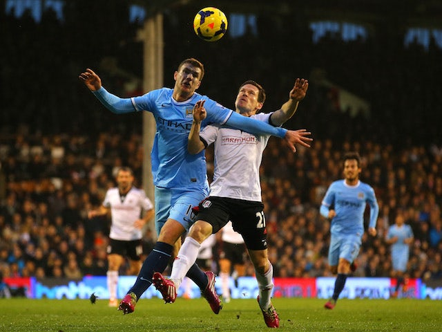 Edin Dzeko of Manchester City and Sascha Riether of Fulham battle for the ball during the Barclays Premier League match on December 21, 2013
