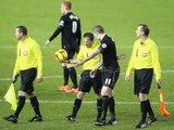 James McClean of Wigan Athletic talks to referee Keith Stroud, after the match is called off due to a waterlogged pitch during the Sky Bet Championship match against Sheffield Wednesday on December 18, 2013