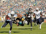 Shonn Greene of the Tennessee Titans runs through Josh Evans of the Jacksonville Jaguars during a game at EverBank Field on December 22, 2013
