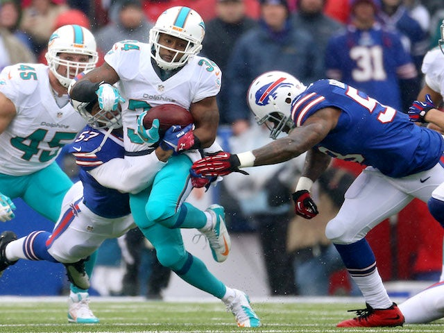 Marcus Thigpen of the Miami Dolphins is tackled as he returns a kick during NFL game action against the Buffalo Bills at Ralph Wilson Stadium on December 22, 2013