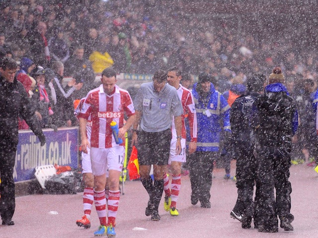 Referee Mark Clattenburg brings the players off as heavy rain falls and play is halted during the Capital One Cup Quarter Final match between Stoke City and Manchester United on December 18, 2013