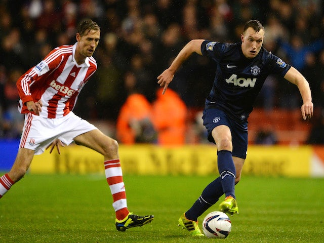 Phil Jones of Manchester United competes with Peter Crouch of Stoke City during the Capital One Cup Quarter Final match on December 18, 2013