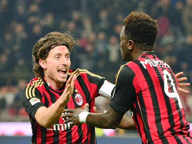 Milan's Sulley Muntari celebrates with teammate Riccardo Montolivo after scoring his team's second goal against Roma during their Serie A match on December 16, 2013