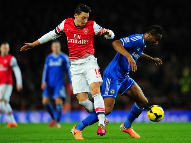 Mesut Ozil of Arsenal and John Obi Mikel of Chelsea compete for the ball during the Barclays Premier League match between Arsenal and Chelsea at Emirates Stadium on December 23, 2013