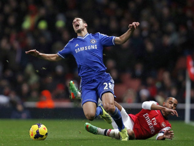 Chelsea's Spanish defender Cesar Azpilicueta is tackled by Arsenal's English striker Theo Walcott during the English Premier League football match between Arsenal and Chelsea at the Emirates Stadium in London on December 23, 2013