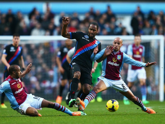 Cameron Jerome of Crystal Palace is tackled by Fabian Delph and Karim El Ahmadi of Aston Villa during the Barclays Premier League match between Aston Villa and Crystal Palace at Villa Park on December 26, 2013