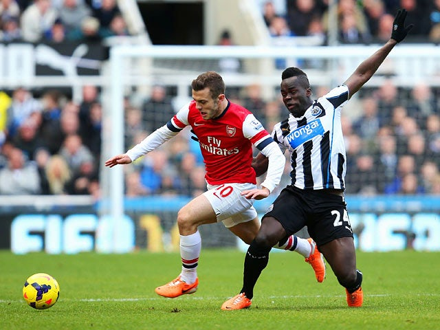 Newcastle's Cheick Tiote and Arsenal's Jack Wilshere battle for the ball during their Premier League match on December 29, 2013