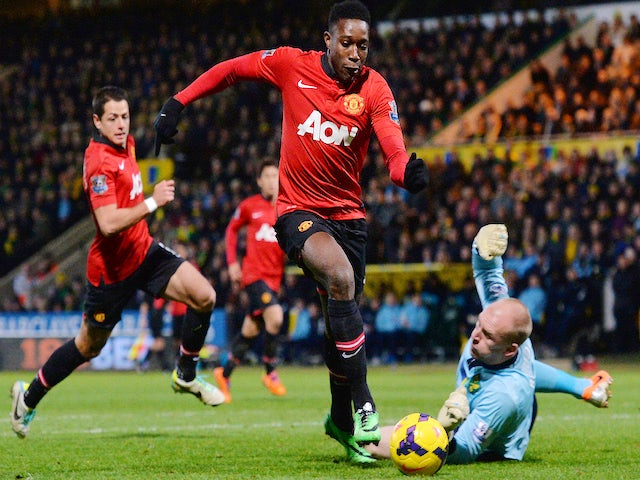 Manchester United's English striker Danny Welbeck scores the opening goal past Norwich City's English goalkeeper John Ruddy (R) during the English Premier League football match on December 28, 2013