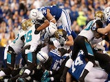 Donald Brown of the Indianapolis Colts dives over the pile of Jacksonville Jaguars defenders for a fist quarter touchdown at Lucas Oil Stadium on December 29, 2013