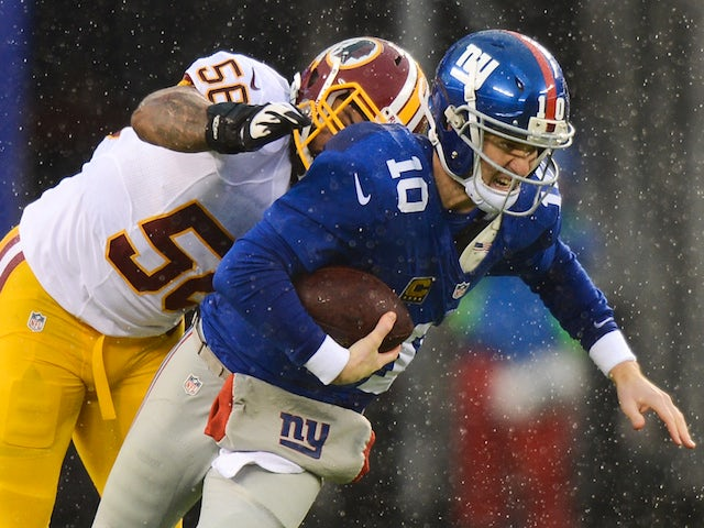 Quarterback Eli Manning of the New York Giants is sacked by inside linebacker Perry Riley #56 of the Washington Redskins on December 29, 2013